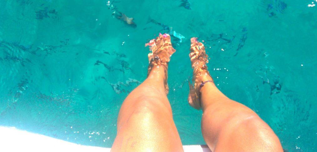catamaran charter ibiza, feet in crystal clear water