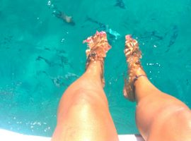 catamaran charter ibiza, feet in crystal clear water