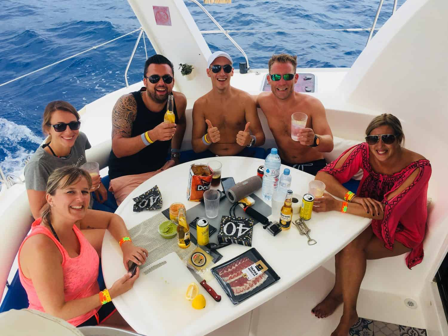 happy group in the exterior saloon of our catamaran Ibiza