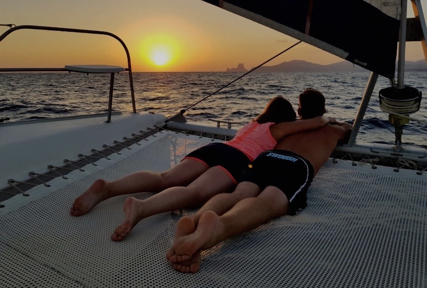 Ibiza catamaran charter, couple on the net enjoying the sunset