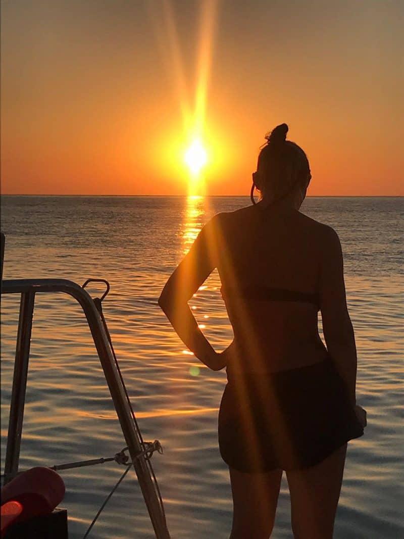 Fille vue de dos au coucher du soleil
