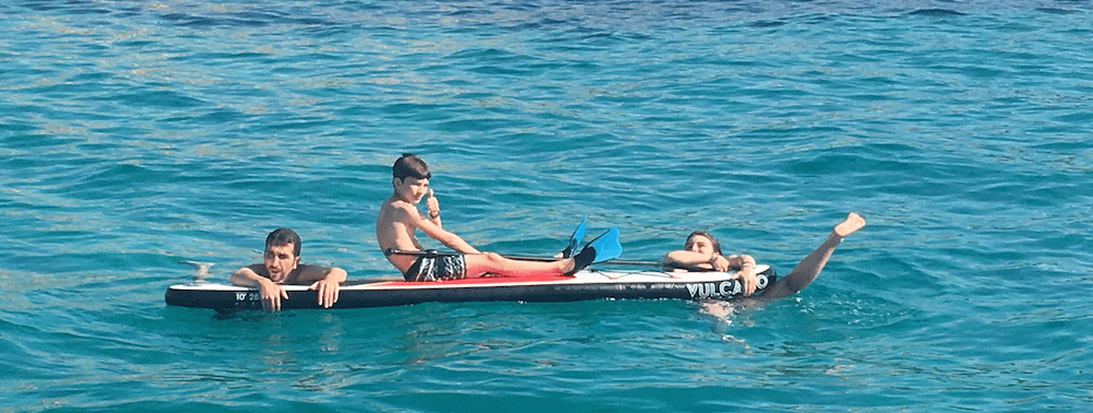 family catamaran in Ibiza with children - father and children paddle surfing.