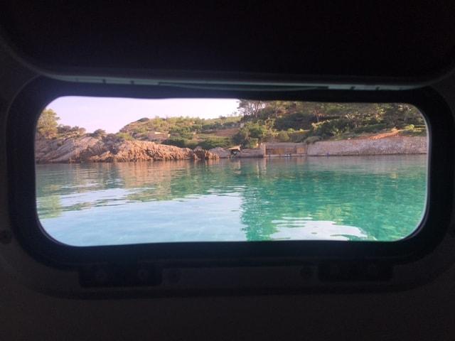 Vue d'une cabine sur une crique à travers l'écoutille d'une des cabines du catamaran à Ibiza.