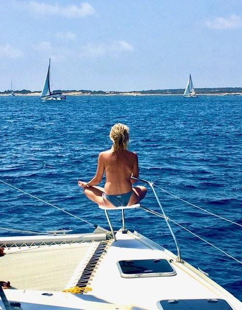 Fille en pose de méditation sur le balcon avant du catamaran à Formentera